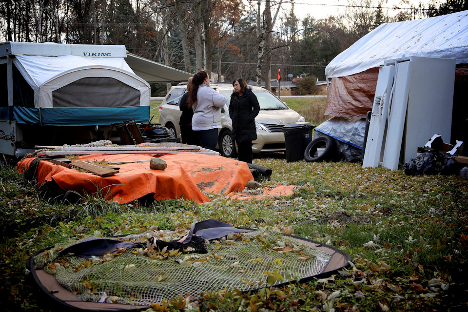 UMCOR case managers speak with a homeowner living in a tent.