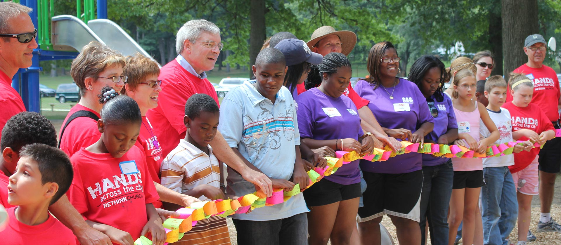 Diverse group of volunteers holding paper chain