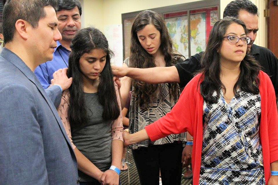 Rev. Rey Mondragon blessing Hispanic youth