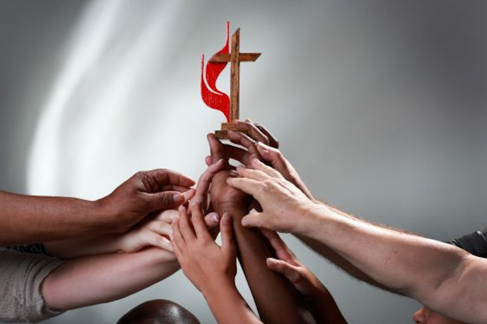 Many hands holding up a United Methodist Cross & Flame