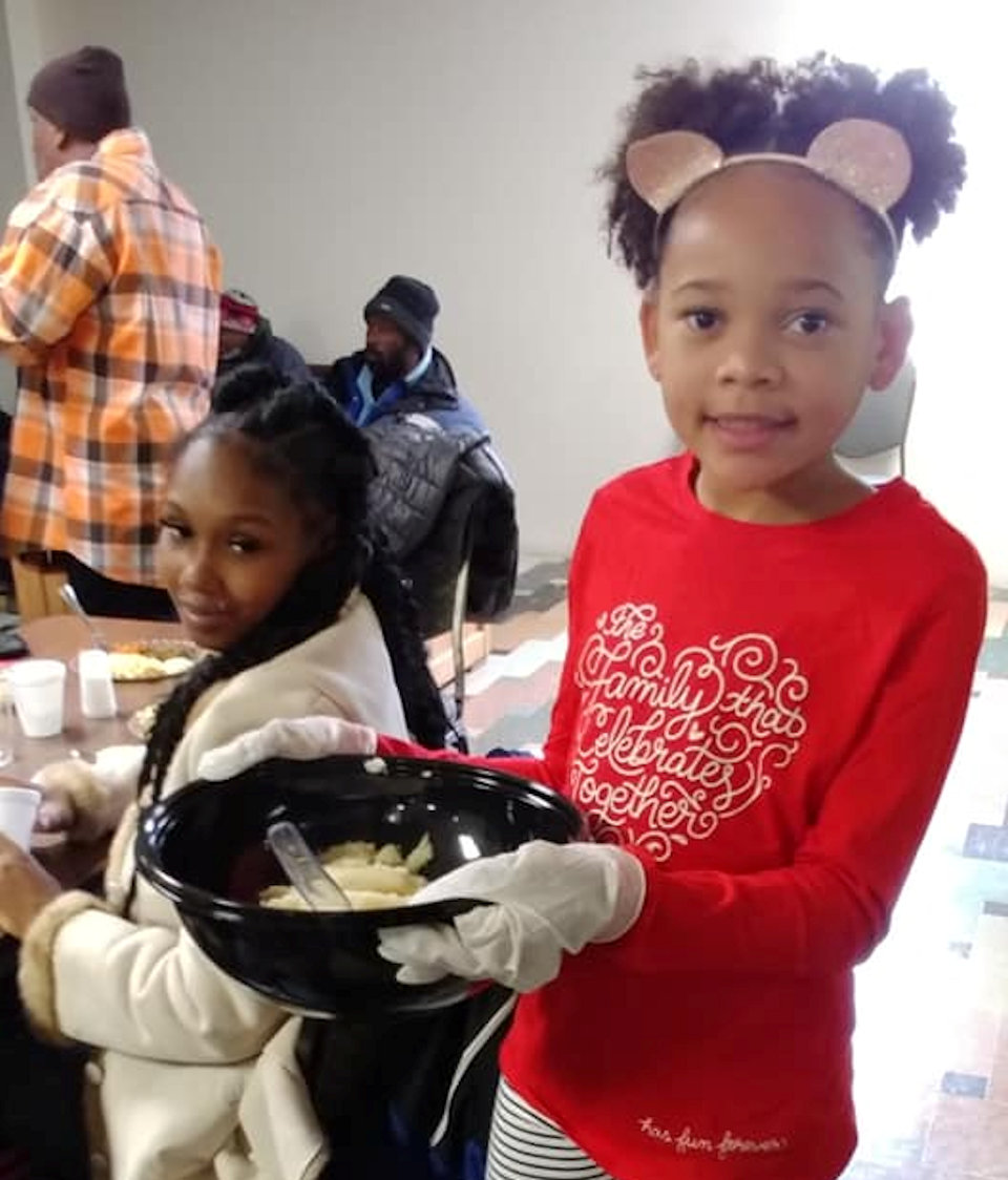 Girl serving Thanksgiving dinner at Cass Community Social Services