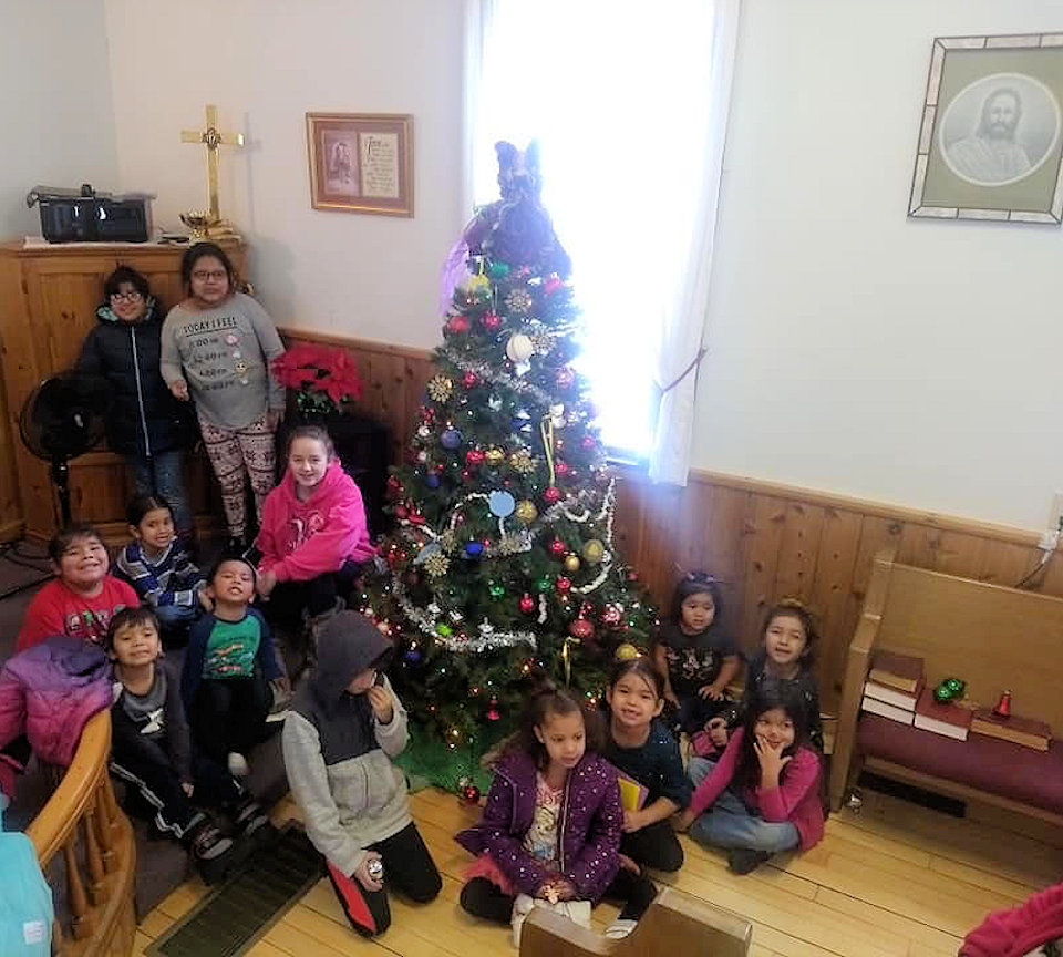 Kids trim the tree at Kewadin Indian Mission