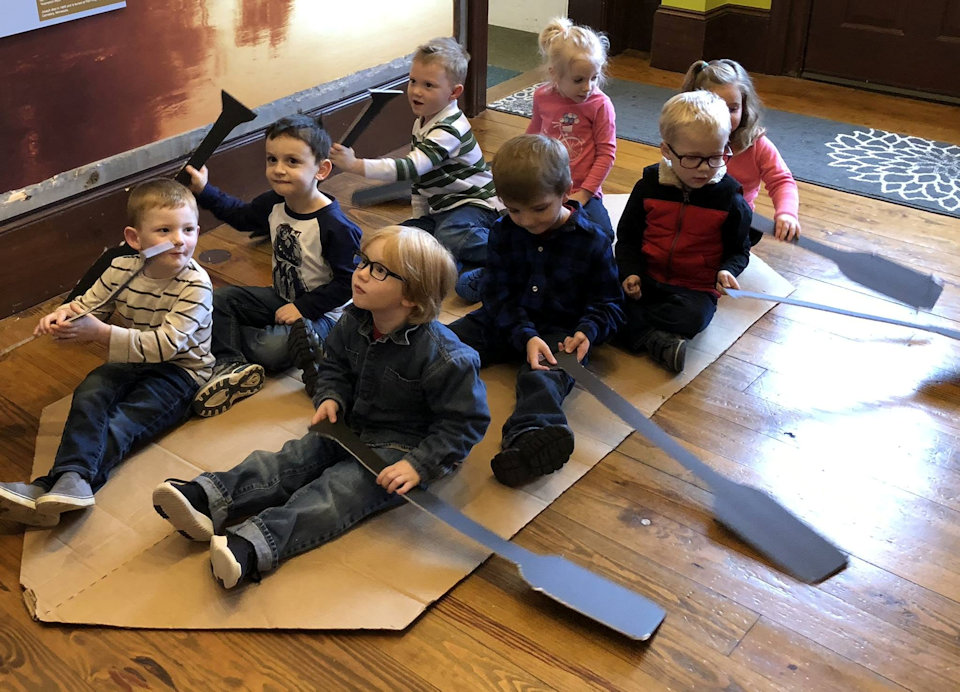 children in a pretend cardboard boat