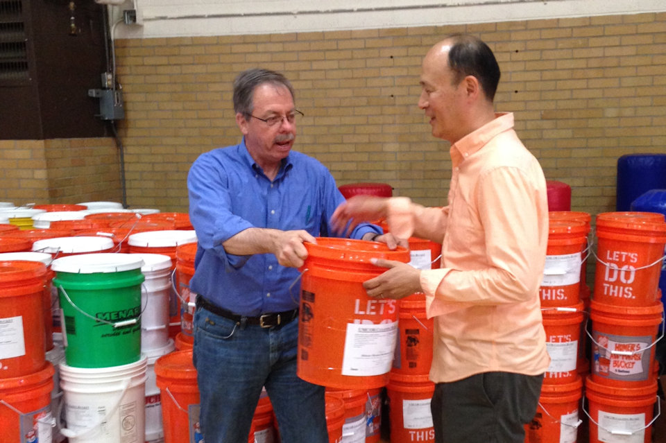 David Kim and Bob Miller unload cleaning buckets