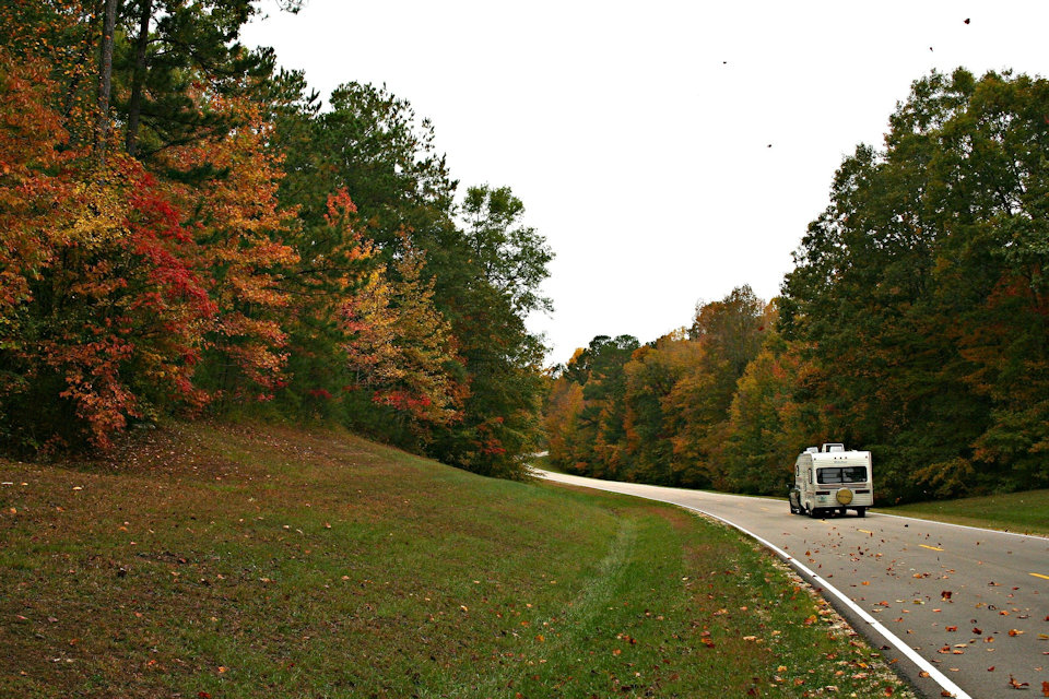 RV traveling down the road in autumn.