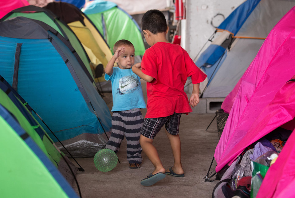 Migrant children playing among tents at Tijuana border