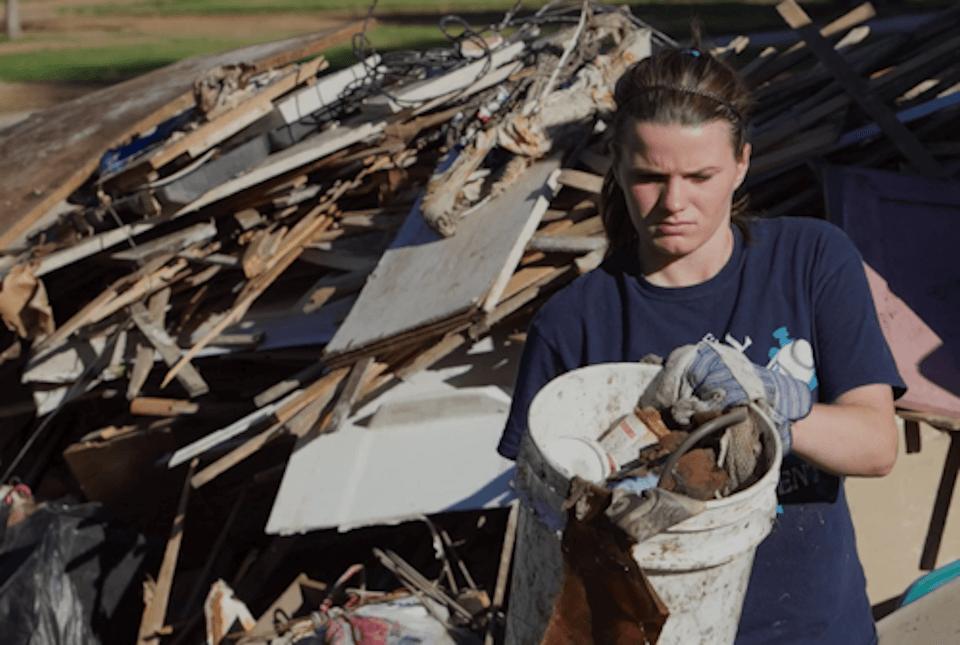 Woman removing storm debris.
