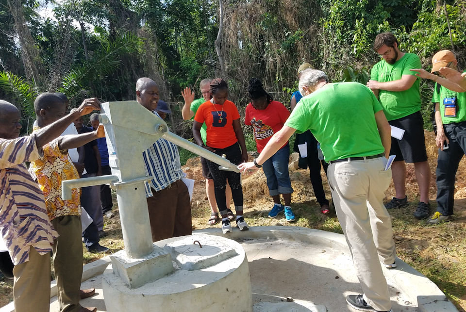 Liberians and Michigan VIMs holding hands and dedicating a well in nohor of Billie Rench.