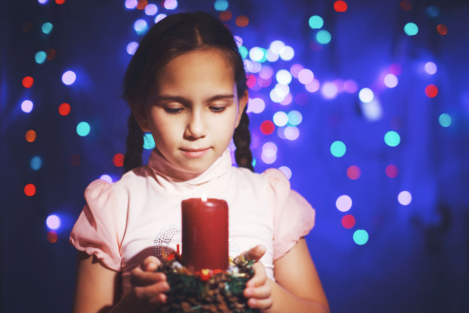 Girl gazing at Advent candle