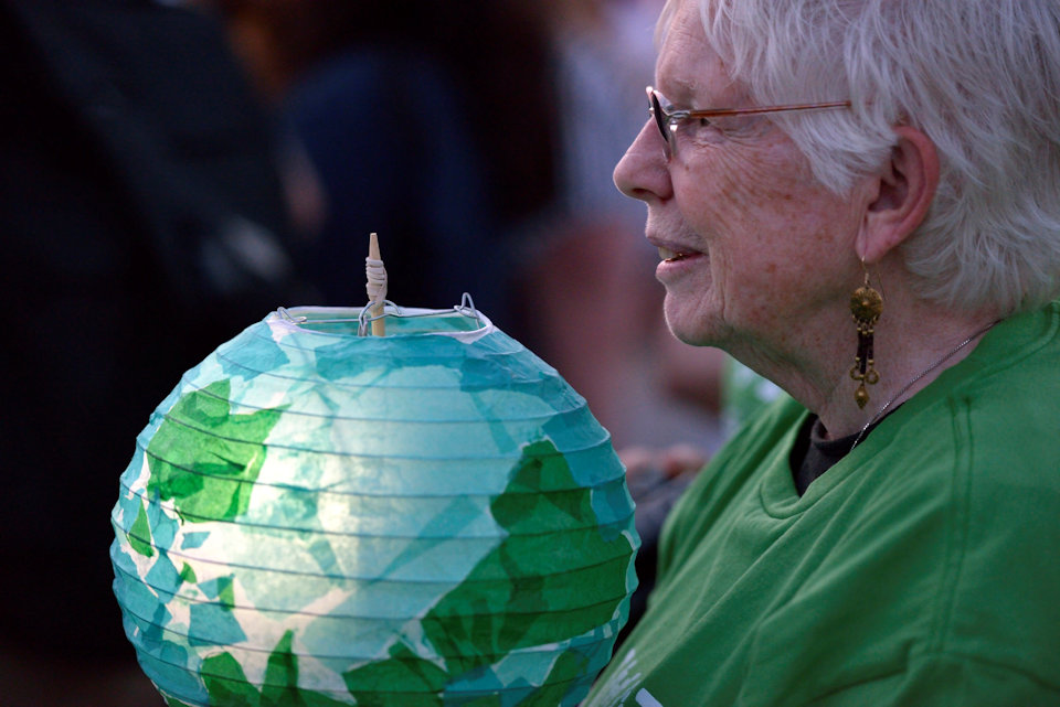 Woman holding lantern resembling world globe