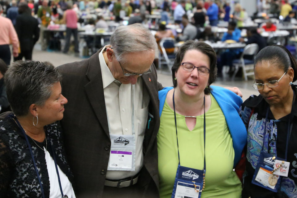Michigan delegates pray at 2016 General Conference.