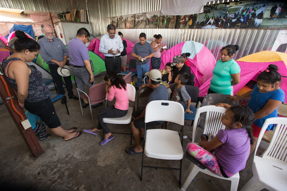 Methodist Bishop of Mexico prays with migrants in center in Tiajuna. Mexico.