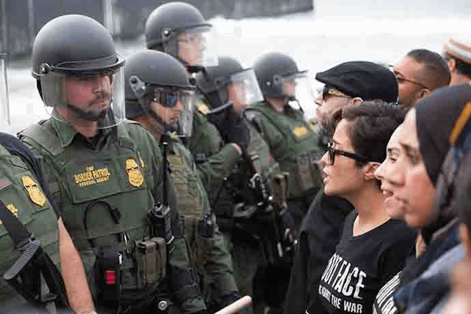 Protesters face to face with border patrol agents.