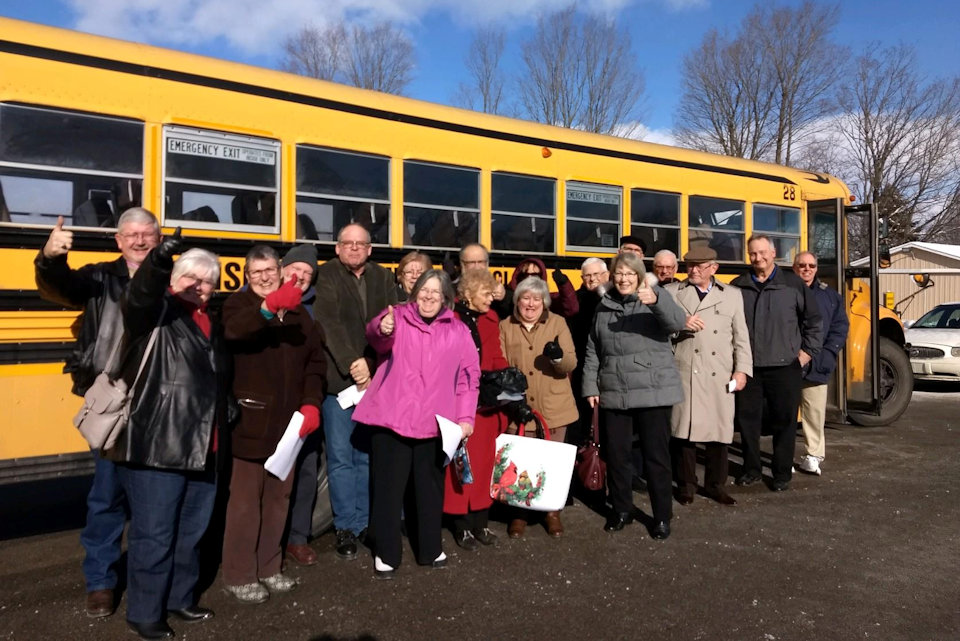 Gladwin UMC members pose with the bus they purchased for ministry.