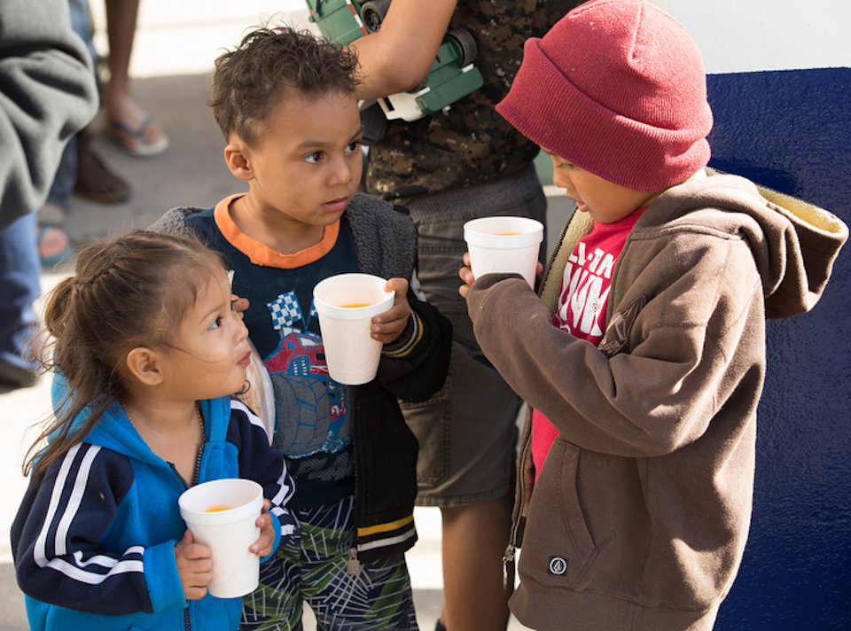 Migrant children wait for meal