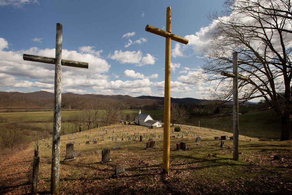 Three crosses stand above a country church