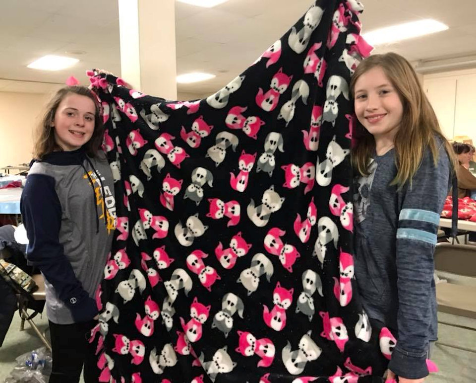 Girls holding a blanket for Project Linus