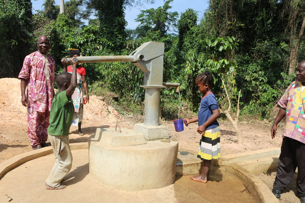 Children pump water in Guinea