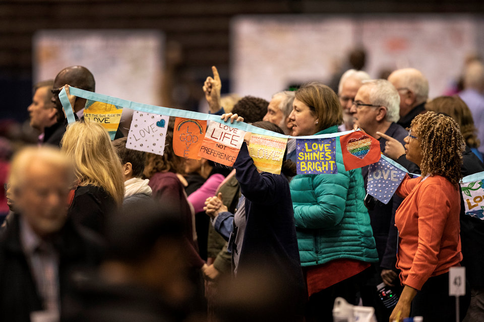 Prayer flags march through the 2019 General Conference.