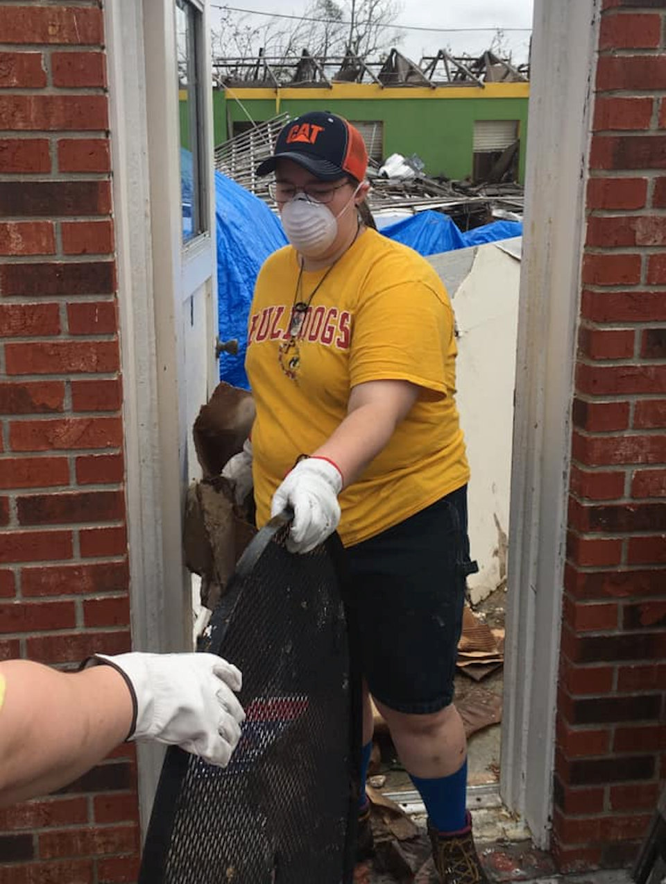 Young person helping clean up hurricane damage