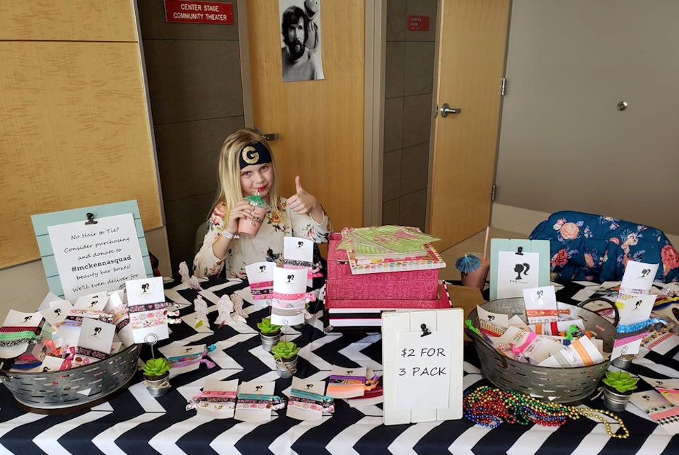 Girl at sales table.