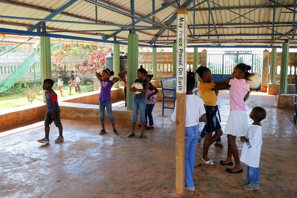 Children play around a Peace Pole in Mizak, Haiti.