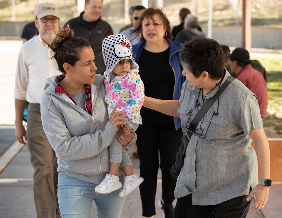 Deaconness at the US-Mexican border with mother and infant.