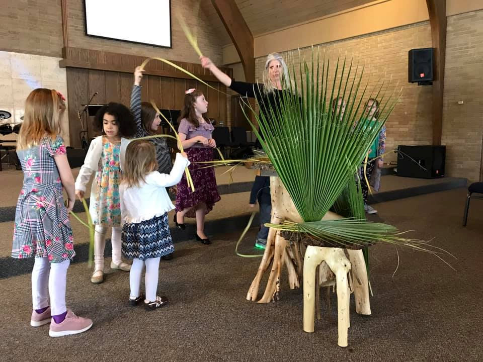 Children and pastor with palm fronds