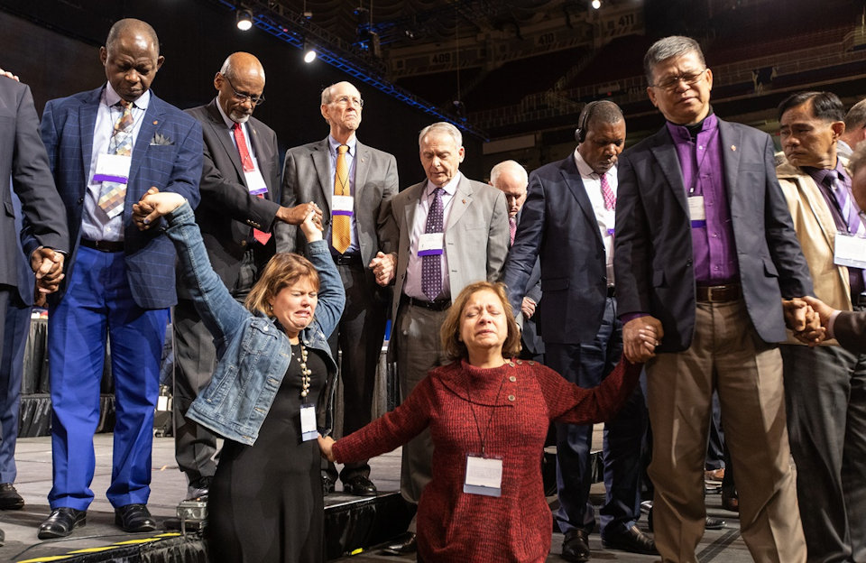 Delegates and bishops pray at General Conference before a crucial vote.