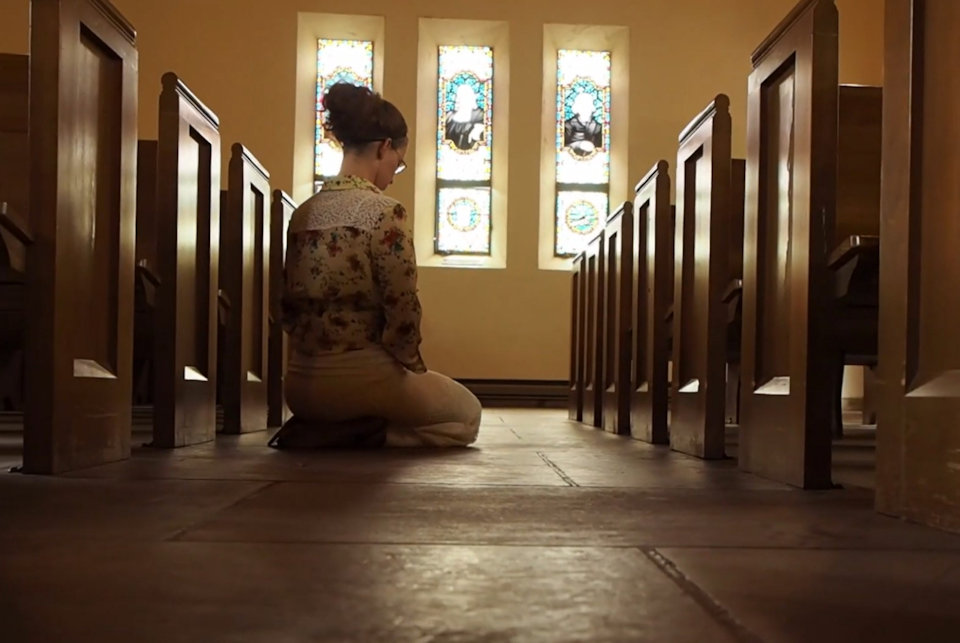 Woman kneeling in a church sanctuary