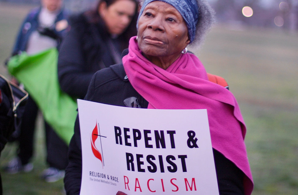 Woman holds sign about ending racism