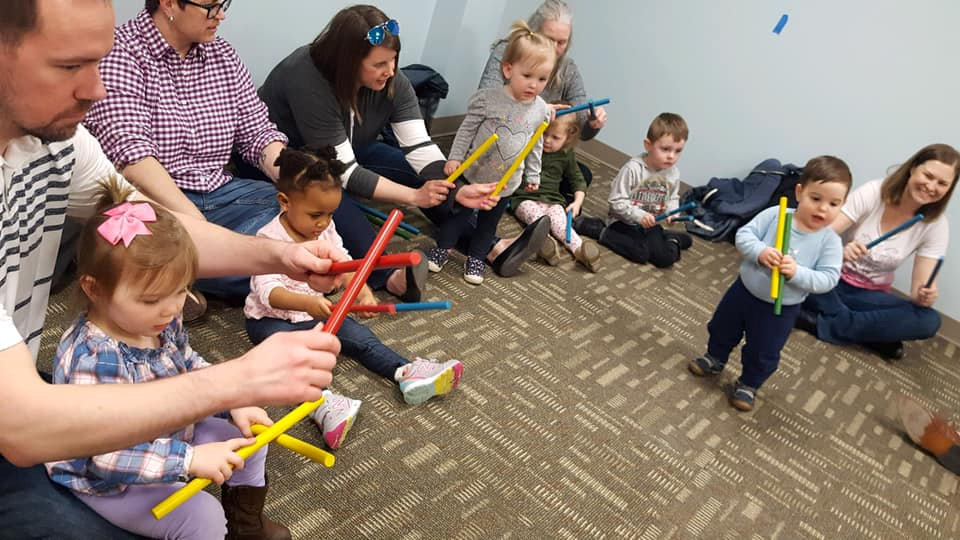 Children and parents with rhythm sticks