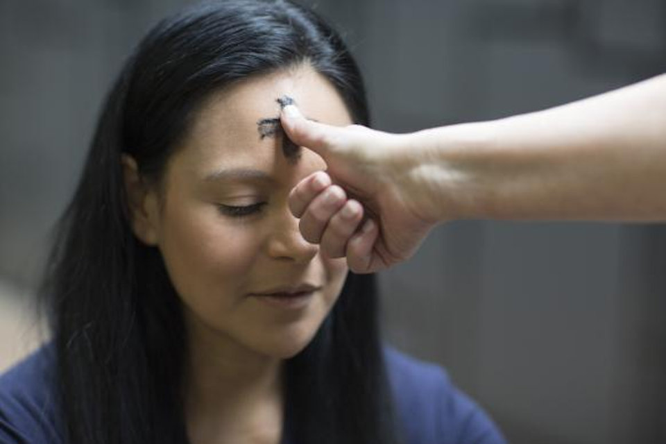 Woman receiving ashes on her forehead.