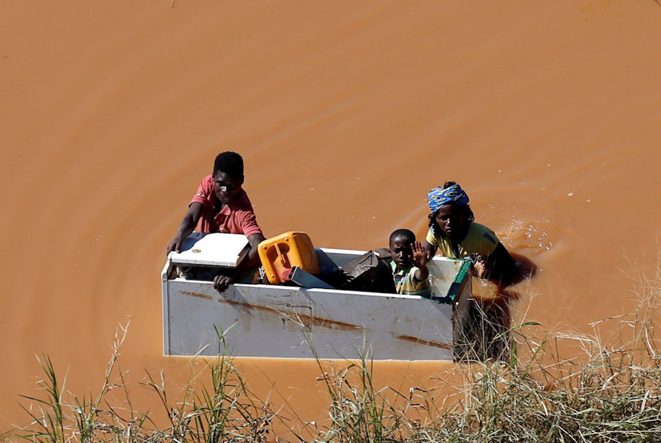 Family in a box floating on flood waters