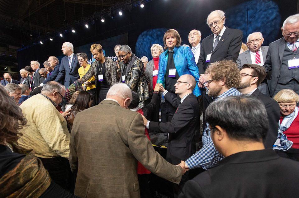 Delegates and Bishops pray together during 2019 General Conference.