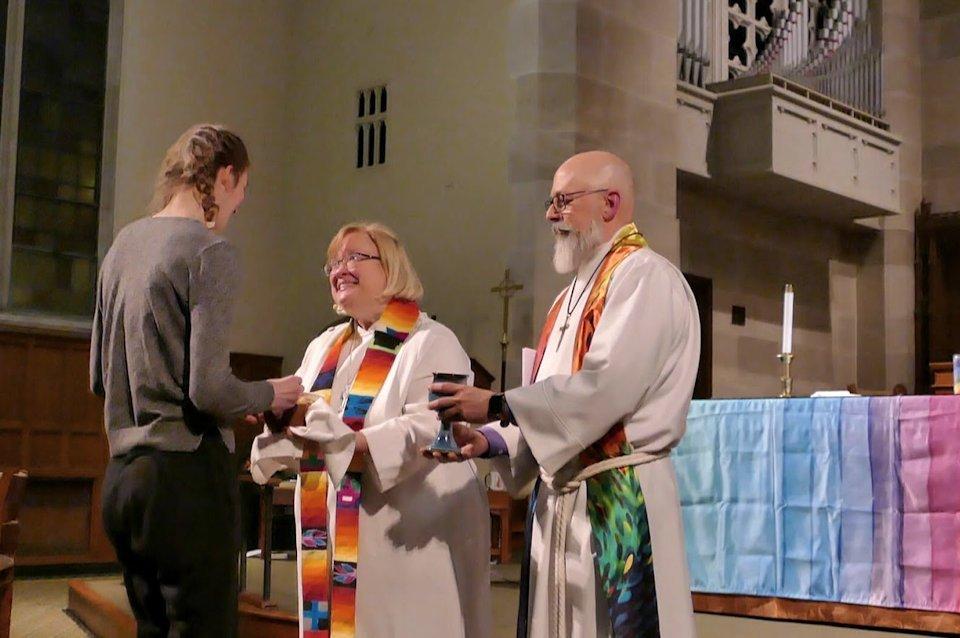 Pastors serve communion to a young woman