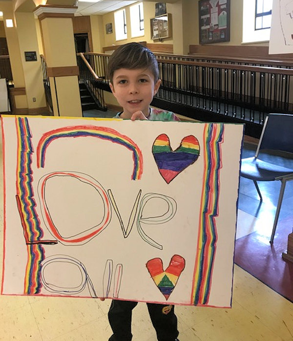 Young boy holds up welcome poster.