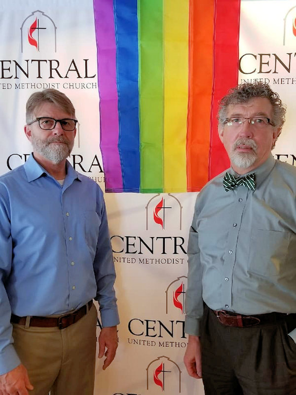 Pastors of Traverse City: Central United Methodist Church stand with rainbow sign of welcome.