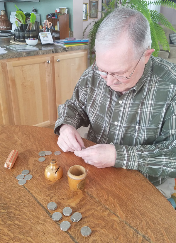 Man counting coins out of small wooden bank.