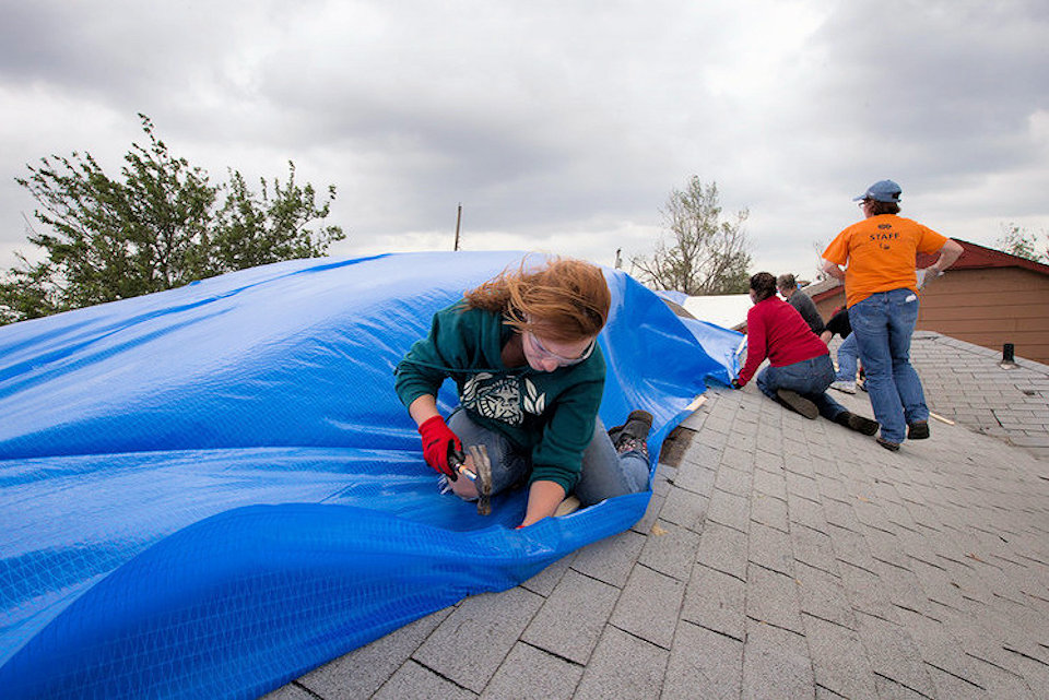 woman fixes tarp to a roof