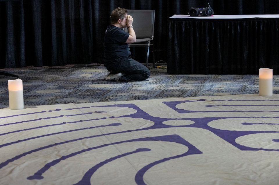 Woman praying at General Conference 2019