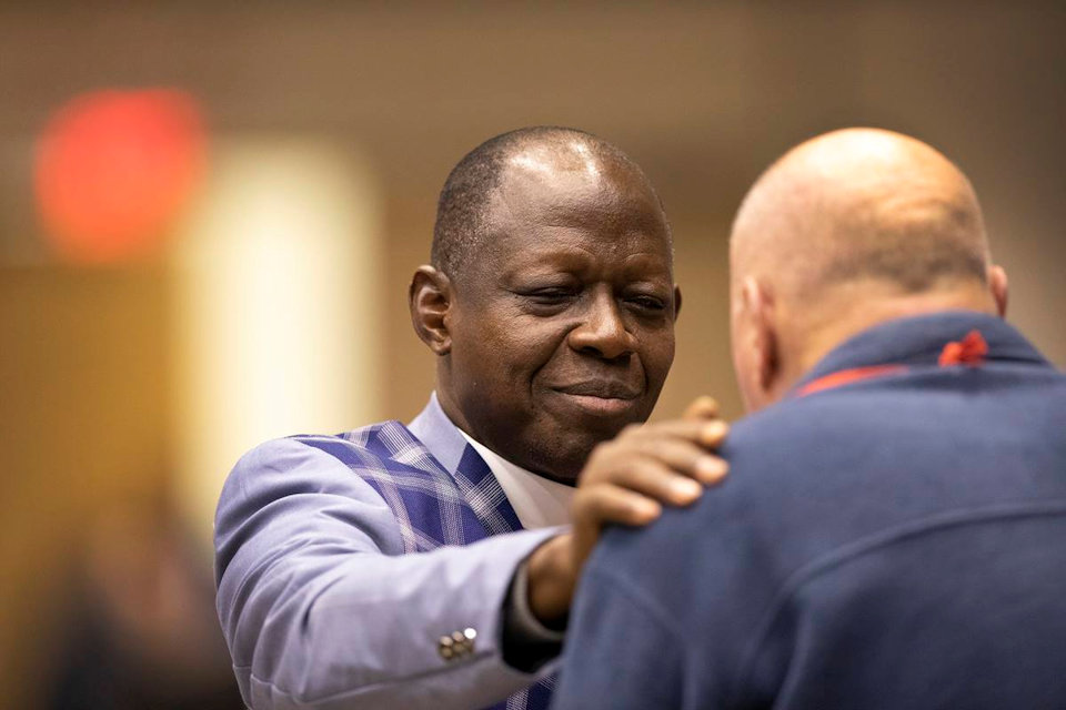 Bishop John Yambasu prays at the 2019 General Conference