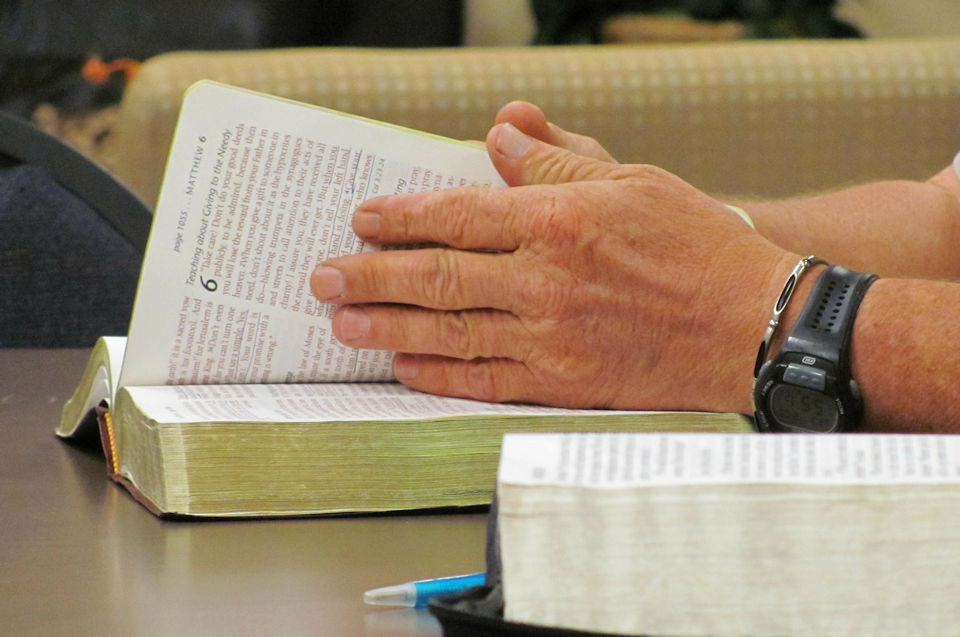 Man searching pages of Bible