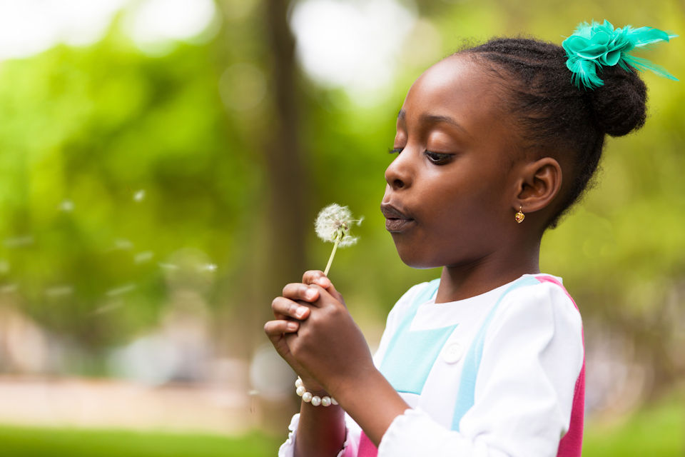 Girl blowing a dandelion head