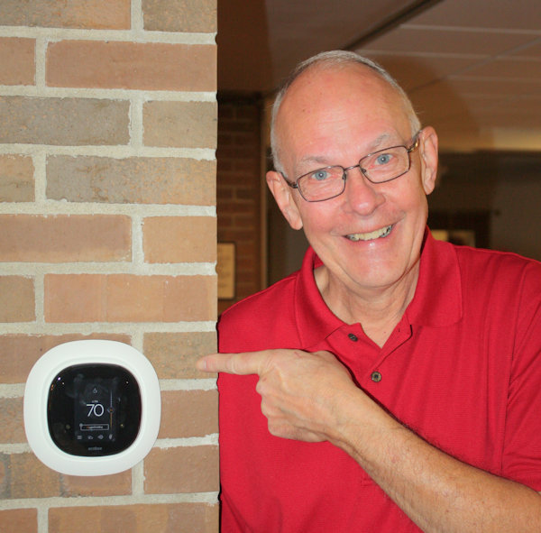 Man pointing at thermostat