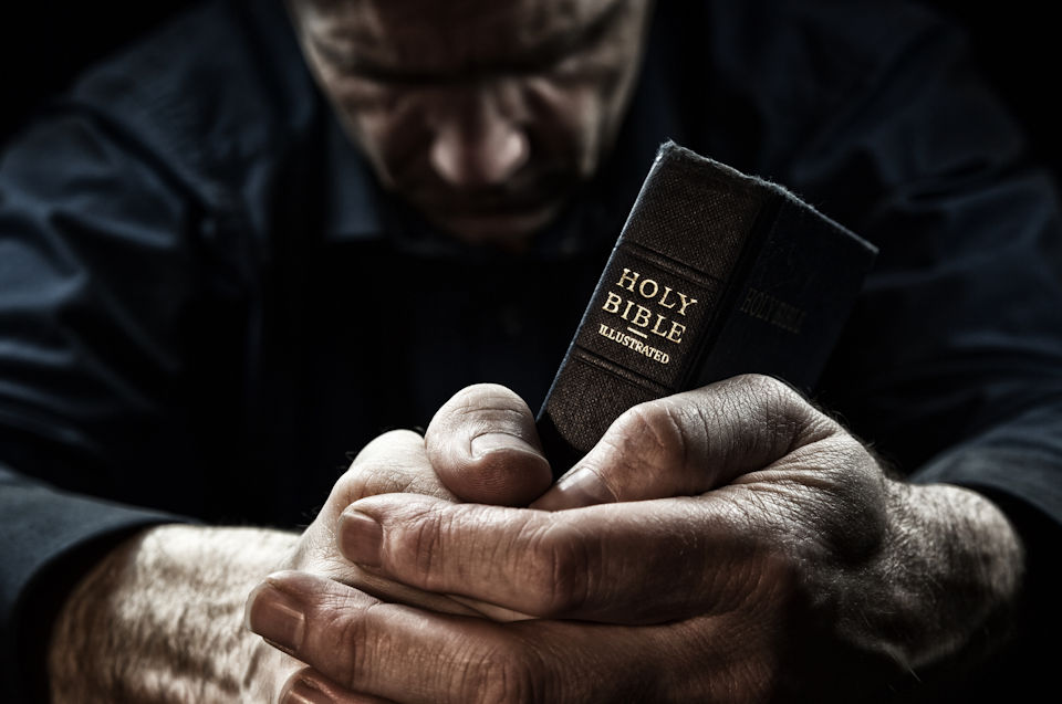 Man in prayer with Bible preparing to be an evangelist.