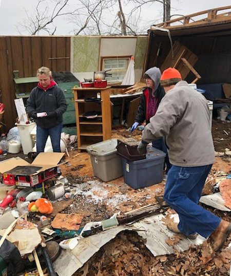 Volunteers sift through tornado debris.