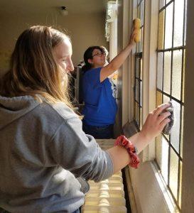 Young women washing windows