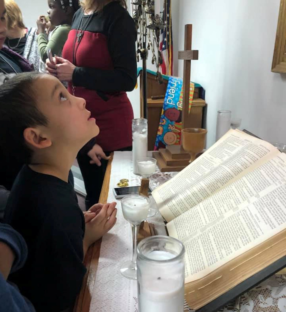 Child looks at the altar cross
