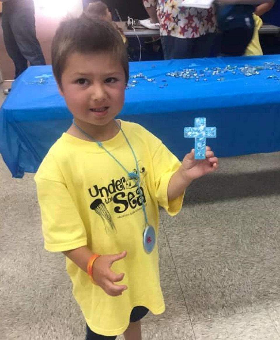 Boy holding cross made at VBS.